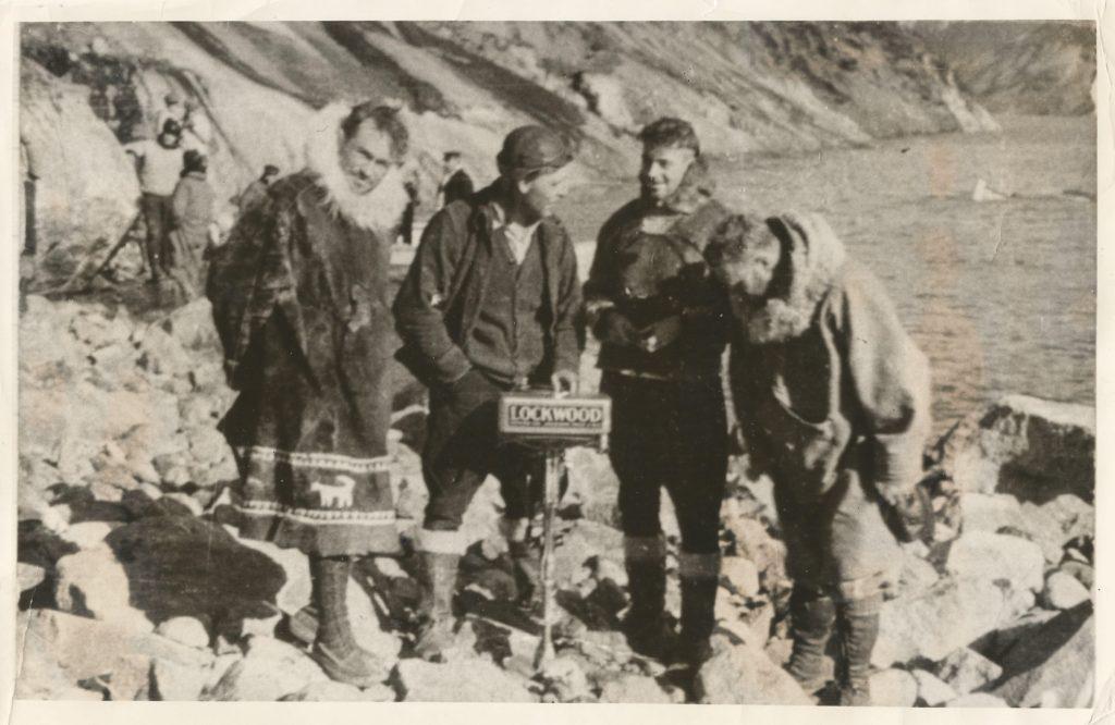 Parker Cramer, Elmer Etes, Duncan Stewart och Bert Hassell efter räddningen. Elmer håller utombordsmotorn från båten de använde för att plocka upp flygaressen med. Ur Midway Village Museums samlingar, Rockford, Illinois, USA.