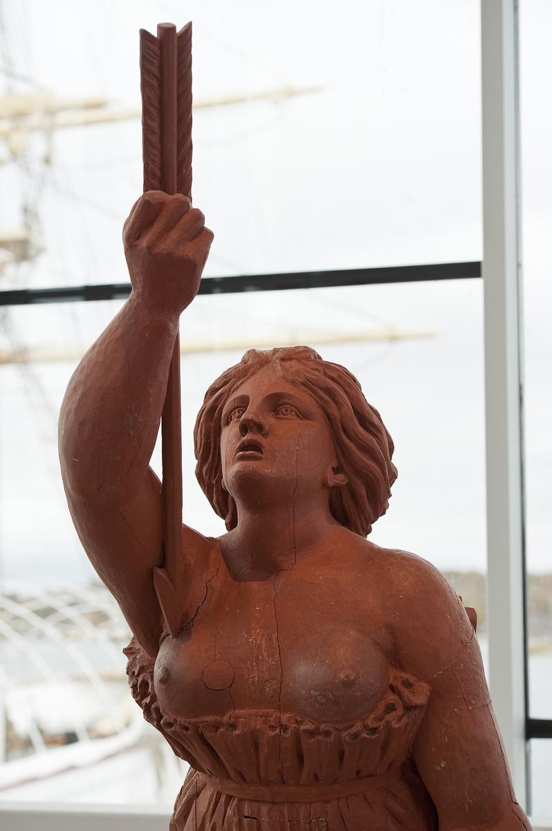 Camillas galjonsfigur, Johan Törnström 1787. Kvinna med naken överkropp iklädd kjol fäst med band under bröstet. Högra armen sträckt framför kroppen, hållande en pil vänd mot högra bröstet. Vänstra armen föres längs sidan med handflatan framåt. Huvudet något bakåtkastat. Färg: Röd (tidigare vit) Foto: Erling Klintefors, Marinmuseum. Källa: https://digitaltmuseum.se/021015563846/mm08335. Licens: https://creativecommons.org/licenses/by-sa/4.0/deed.sv.